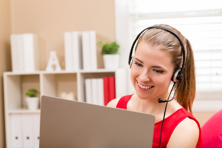 Happy young woman using her laptop and headset at home