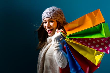 Szczęśliwi młodej kobiety mienia torba na zakupy na zmroku - błękitny tło