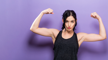Powerful young fit woman on a solid background