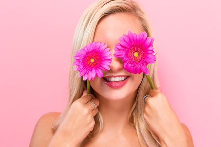 Young woman with pink garberas on a pink background