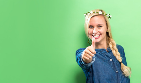 Happy young woman giving a thumb up on a solid background