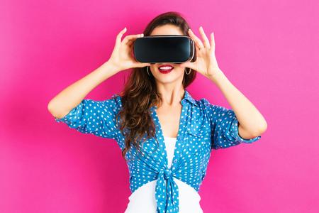 Gelukkige jonge vrouw die een virtuele werkelijkheidshoofdtelefoon met behulp van