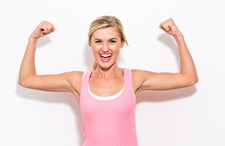 Powerful young fit woman on a white background