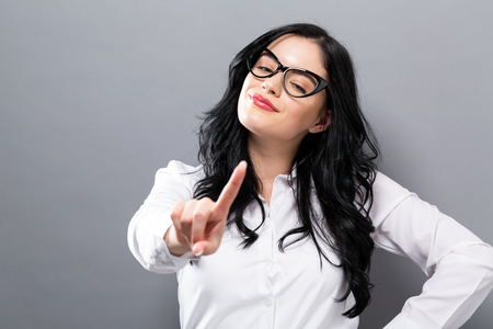 Young woman pointing something on a solid background