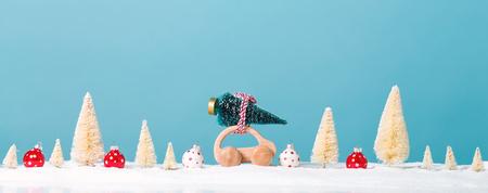 Hölzernes Miniaturauto, das einen Weihnachtsbaum auf einem blauen Hintergrund trägt