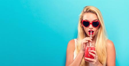 Gelukkige jonge vrouw die smoothie op een stevige achtergrond drinken Stockfoto
