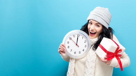 Young woman holding a clock showing nearly 12 Foto de archivo