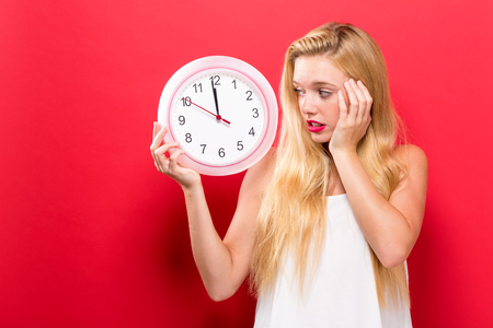 Young woman holding a clock showing nearly 12 版權商用圖片