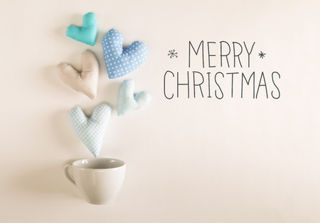 Merry Christmas message with blue heart cushions coming out of a coffee cup Stock Photo