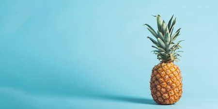 Whole pineapple on a bright blue background Imagens