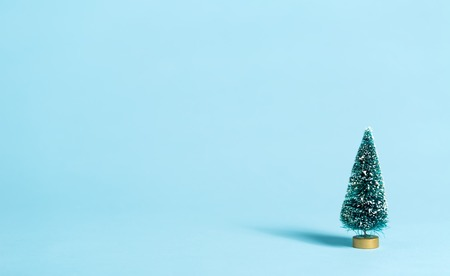 Small green Christmas trees on a blue background Stock Photo