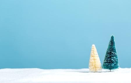雪の中で小さな緑と白のクリスマス ツリー 写真素材
