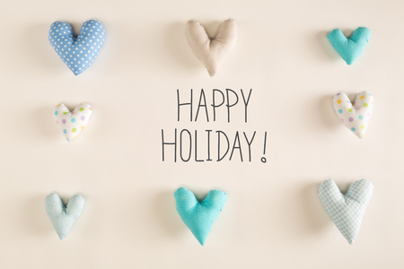 Happy Holiday message with blue heart cushions on a white paper background