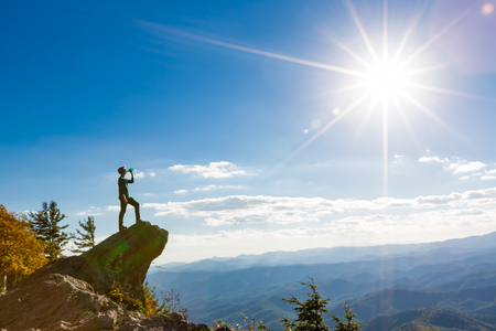 Man with a water bottle at the edge of a cliff overlooking the mountains below Stok Fotoğraf