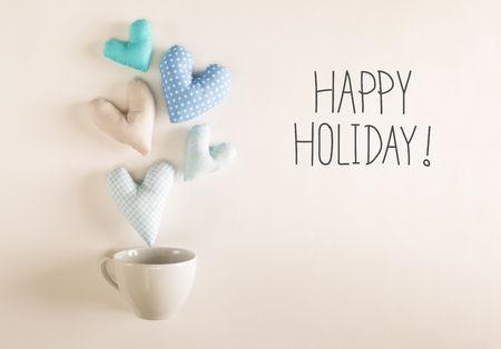 Happy Holiday message with blue heart cushions coming out of a coffee cup