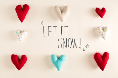 Let It Snow message with blue heart cushions on a white paper background Stock Photo