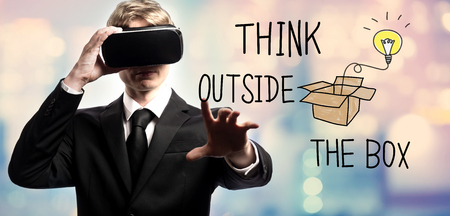 Think Outside The Box text with businessman using a virtual reality headset Stock Photo