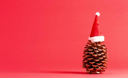赤でサンタハットとクリスマスをテーマにした松毬 写真素材