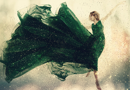 Beautiful woman in a green dress jumping 스톡 콘텐츠