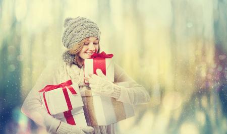 雪の夜にプレゼントボックスを持つ幸せな若い女性 写真素材
