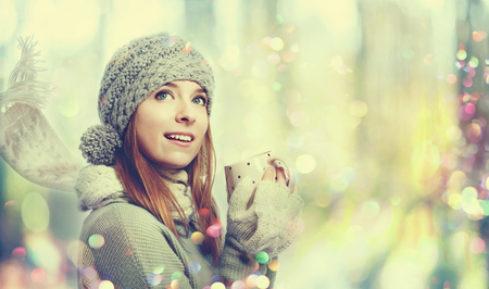 Young woman in winter clothes drinking coffee Stock Photo