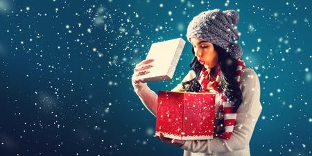 Gelukkige jonge vrouw die een huidige doos van Kerstmis opent Stockfoto