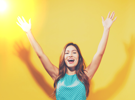 Happy young woman raising her arms on a solid background