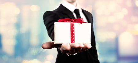 Businessman presenting a gift box on pink and blue abstract light background