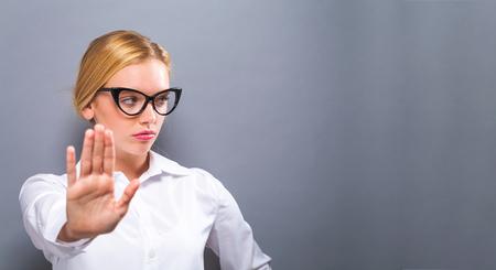 単色の背景をもたらす拒絶を作る若い女性