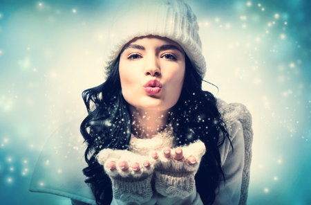 Gelukkige jonge vrouw die met de winterkleren een kus blaast Stockfoto