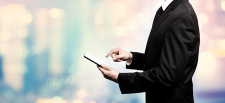 Businessman using a digital tablet on pink and blue abstract light background Stock Photo