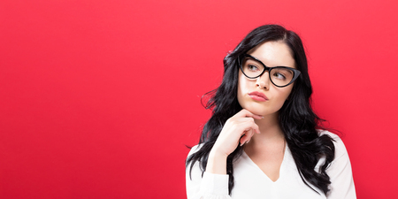 Young businesswoman in a thoughtful pose on a solid background Reklamní fotografie