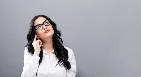 Young businesswoman in a thoughtful pose on a solid background Stock Photo