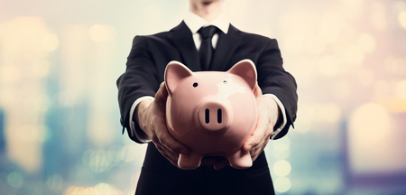 Businessman holding a piggy bank on pink and blue abstract light background Foto de archivo