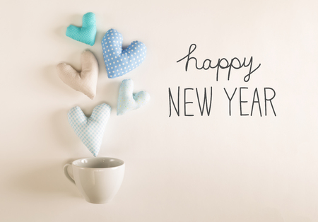 Happy New Year message with blue heart cushions coming out of a coffee cup