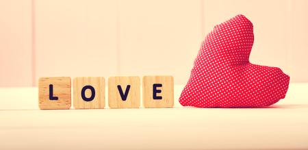 ピンク板に愛のメッセージ付きハートのクッション 写真素材