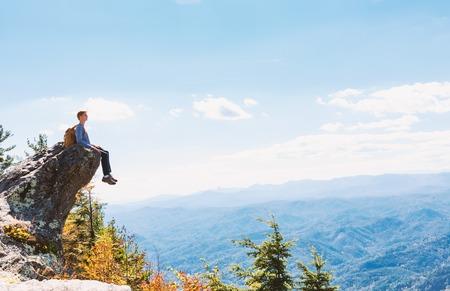 下の山々を見下ろす崖の端に座っている男