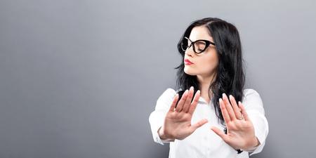 De jonge vrouw die een afwijzing vormt stelt een stevige achtergrond