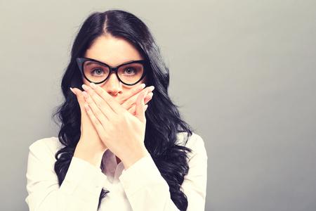 Jonge vrouw die haar mond op een stevige achtergrond Stockfoto