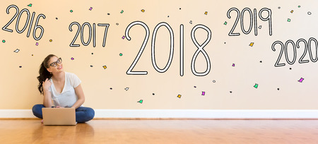 2018 New Year with young woman using a laptop computer on floor Stock Photo
