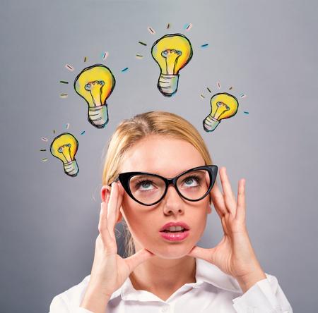 Glühbirnen mit Business-Frau auf einem grauen Hintergrund Standard-Bild - 91687690