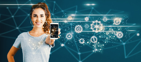 Gears with young woman holding out a smartphone in her hand