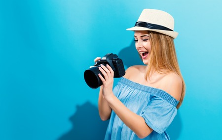 青い背景にカメラを持つ若い女性 写真素材