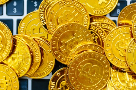 Pile of gold bitcoins on top of a laptop keyboard Stock Photo