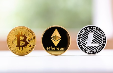 Bitcoin, ethereum and litecoin coins on a bright background