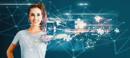 Puzzle Pieces with young woman holding out a smartphone in her hand Stock Photo