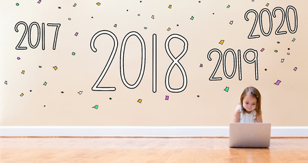 2018 with little girl using a laptop computer on floor Stock Photo
