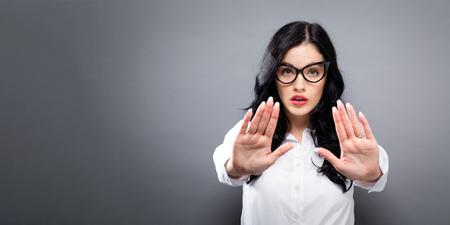 拒絶をする若い女性は、固体の背景をポーズ 写真素材
