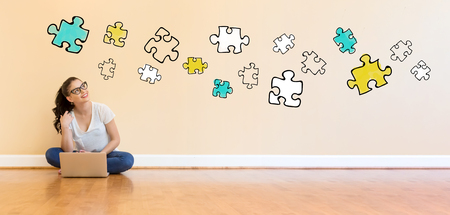 Puzzles with young woman using a laptop computer on floor