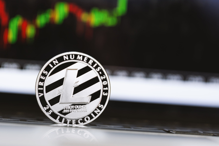 Litecoin crypotocurrency coin with price chart in the background Stock Photo